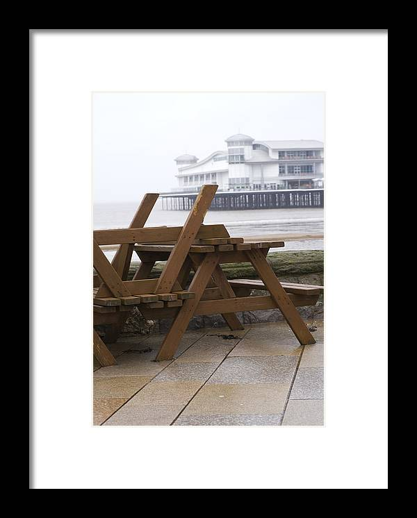 Weston-super-mare Framed Print featuring the photograph Upturned wooden tables at out of season seaside by Lyn Holly Coorg
