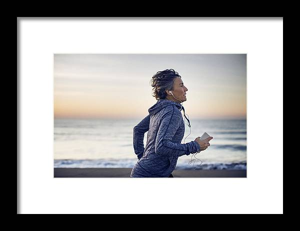 Tranquility Framed Print featuring the photograph Woman jogging while listening music at beach against sky by Cavan Images