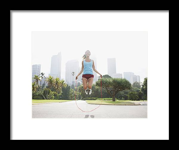 People Framed Print featuring the photograph Woman skipping rope in park by Tom Merton