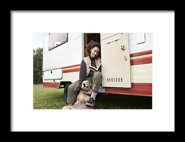Pets Framed Print featuring the photograph Woman with dog reading book in motor van by Klaus Vedfelt