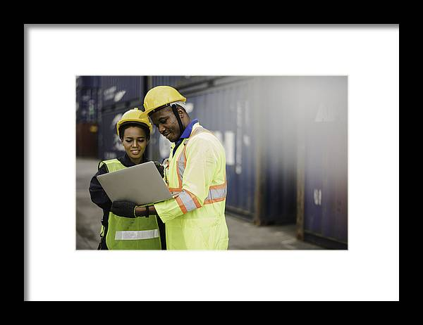 Working Framed Print featuring the photograph Young African american men and woman worker Check and control loading freight Containers by use computer laptop at commercial shipping dock felling happy. Cargo freight ship import export concept by Niphon Khiawprommas