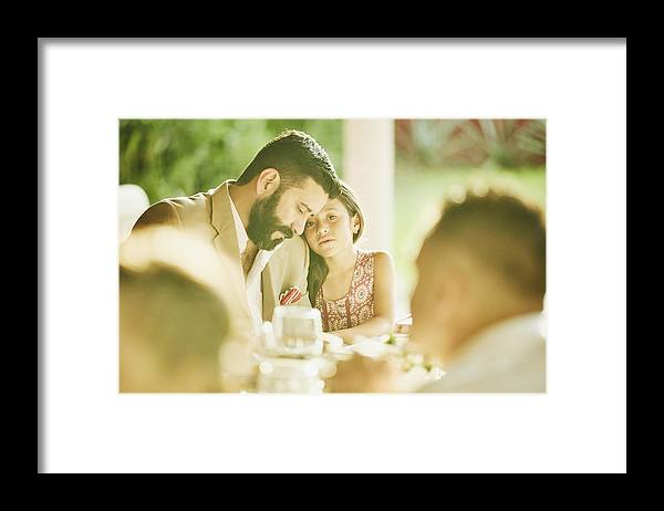 Mature Adult Framed Print featuring the photograph Young girl embracing father during outdoor wedding reception dinner by Thomas Barwick