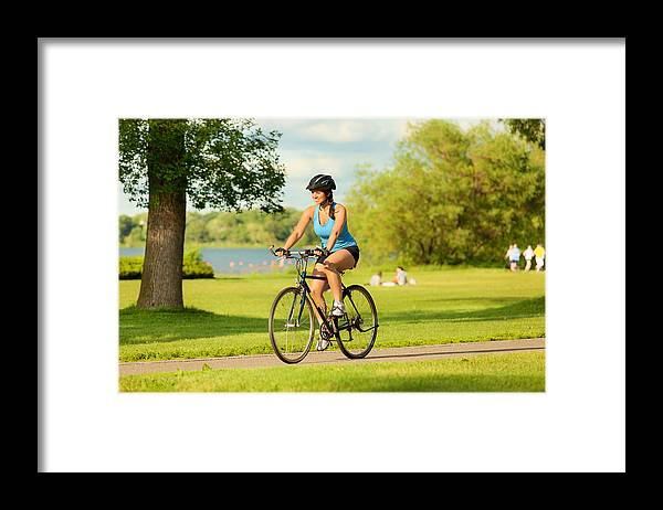 Scenics Framed Print featuring the photograph Young Healthy Woman Exercising on Bicycle in Urban City by YinYang