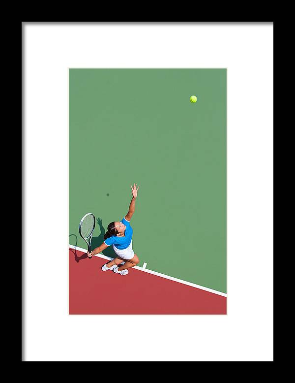 Asian And Indian Ethnicities Framed Print featuring the photograph Young tennis player serving by Nycshooter