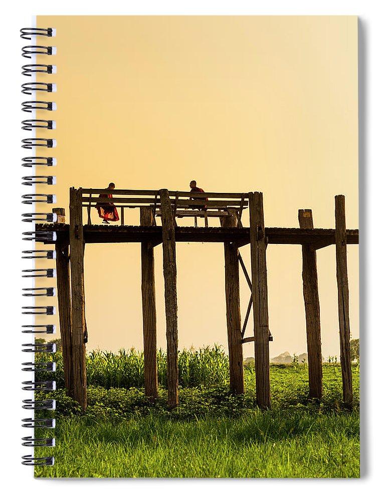 Grass Spiral Notebook featuring the photograph Buddhist Monks Seated On U Bein Bridge by Merten Snijders