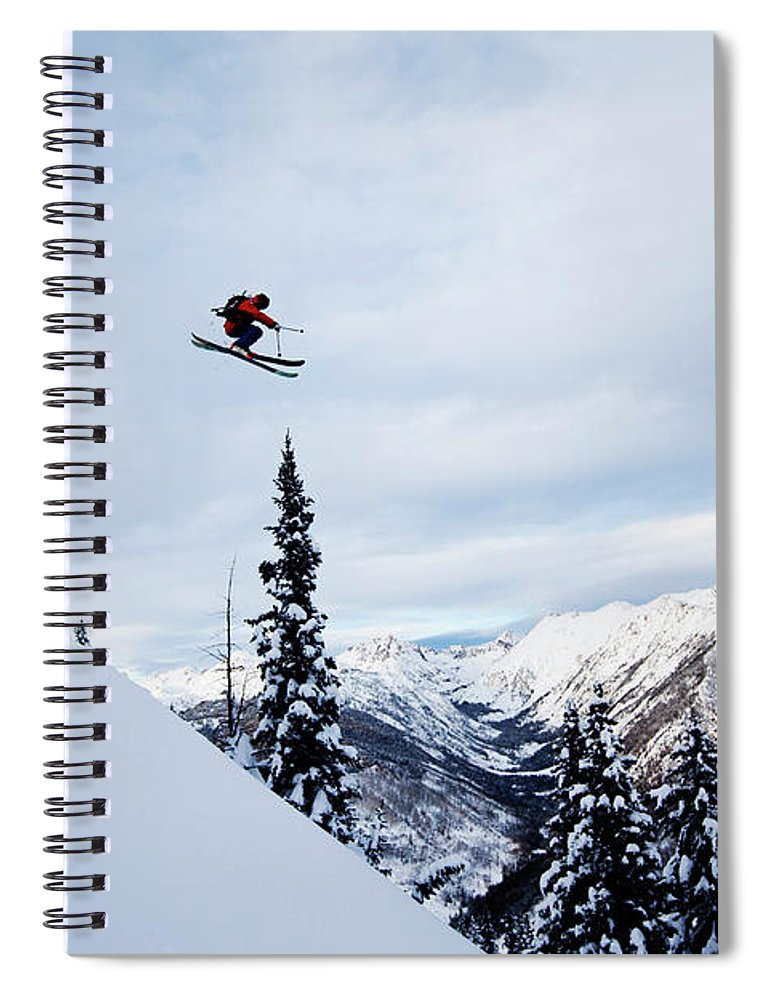 Skiing Spiral Notebook featuring the photograph A Athletic Skier Jumping Off A Cliff In by Patrick Orton