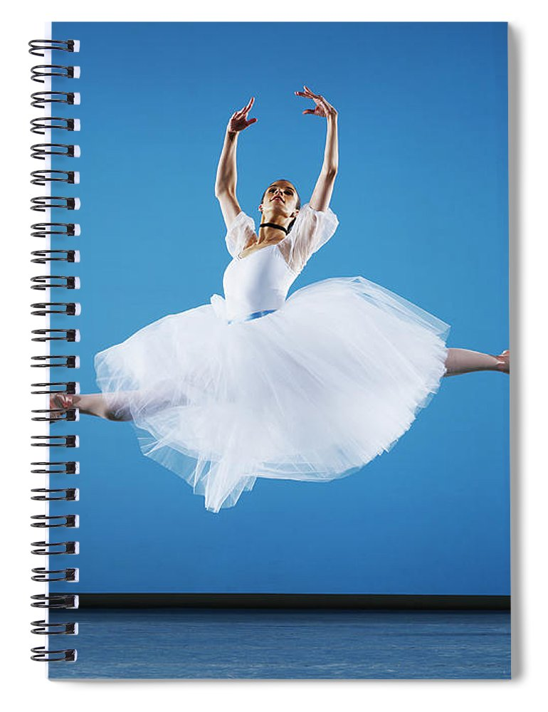 Ballet Dancer Spiral Notebook featuring the photograph Ballerina Leaping On Stage, Arms Raised by Thomas Barwick