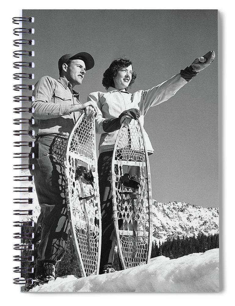 Heterosexual Couple Spiral Notebook featuring the photograph Couple Holding Snowshoes, Woman Pointing by Stockbyte