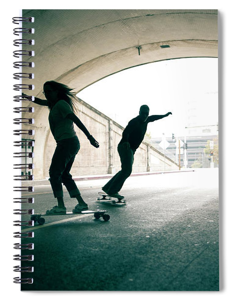 Mature Adult Spiral Notebook featuring the photograph Couple Skateboarding Through Tunnel by Ian Logan