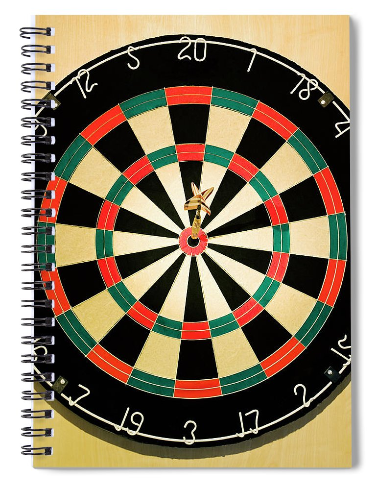 Expertise Spiral Notebook featuring the photograph Dart In Bulls Eye On Dart Board by Fuse