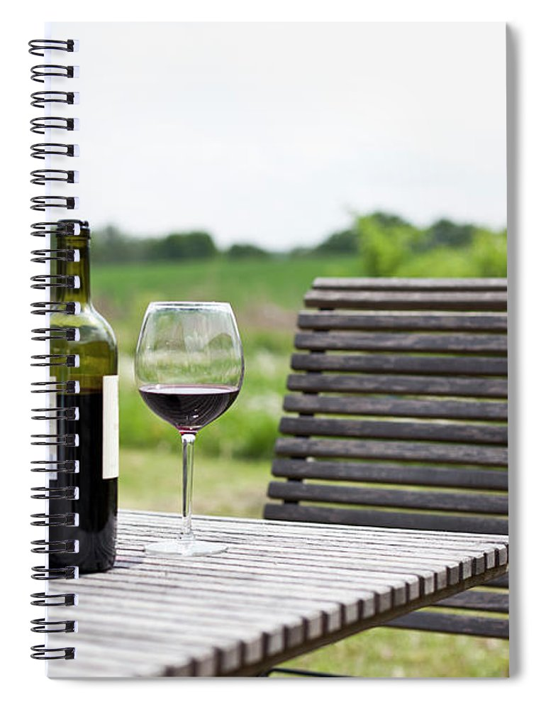 Five Objects Spiral Notebook featuring the photograph Glasses And A Bottle Of Red Wine On An by Halfdark