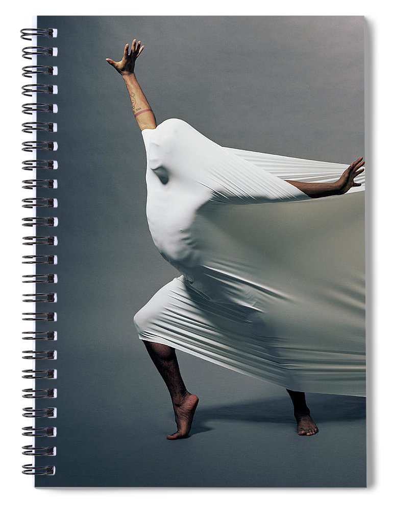 Hand Raised Spiral Notebook featuring the photograph Man Pressing Into Fabric, Arms Extended by Pm Images