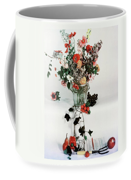 Nobody Coffee Mug featuring the photograph A Studio Shot Of A Vase Of Flowers And A Garden by Herbert Matter