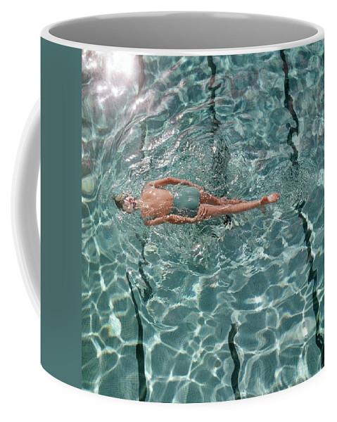 Water Coffee Mug featuring the photograph A Woman Swimming In A Pool by Fred Lyon