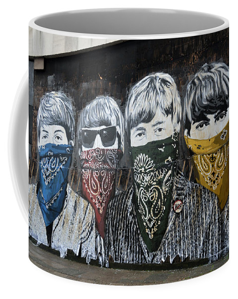 Banksy Coffee Mug featuring the photograph The Beatles wearing face masks street mural by RicardMN Photography