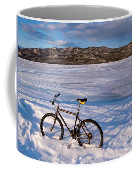 Adventure Coffee Mug featuring the photograph Bike On Frozen Lake Laberge Yukon Canada by Stephan Pietzko