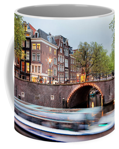 Amsterdam Coffee Mug featuring the photograph Canal Bridge And Boat Tour In Amsterdam At Evening by Artur Bogacki