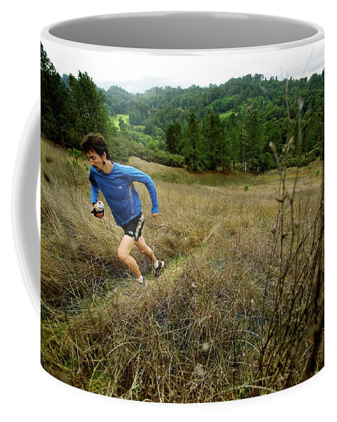 Action Coffee Mug featuring the photograph Man Trail Running On A Foggy Day by Corey Rich