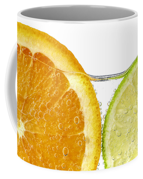 Orange Coffee Mug featuring the photograph Orange And Lime Slices In Water by Elena Elisseeva