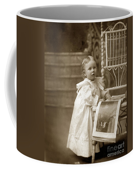 Victorian Little Girl Standing Next To A Wicker Chair Looking At A Book  Circa 1900 Coffee Mug