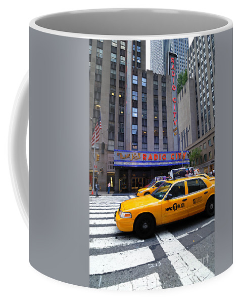 Building Coffee Mug featuring the photograph Yellow Cabs Pass In Front Of Radio City Music Hall by Amy Cicconi
