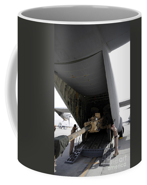 Airlifter Coffee Mug featuring the photograph Aircrew Load An M777 A2 Howitzer Onto by Stocktrek Images