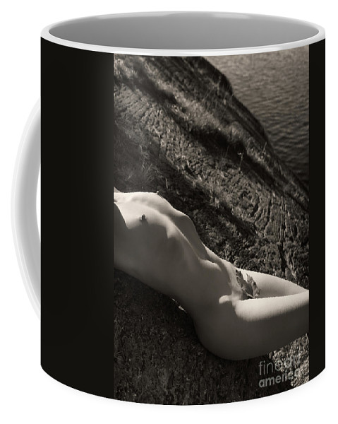 Nude Coffee Mug featuring the photograph Nude Woman Lying On Rocks By The Water by Oleksiy Maksymenko