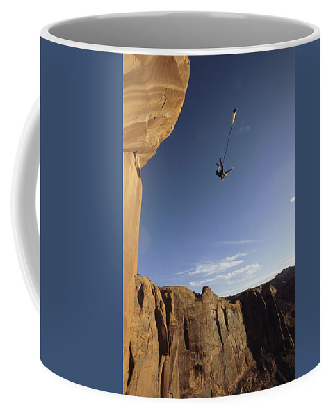 Feats Of Daring Coffee Mug featuring the photograph A Base Jumper Leaping With A Parachute by Jimmy Chin