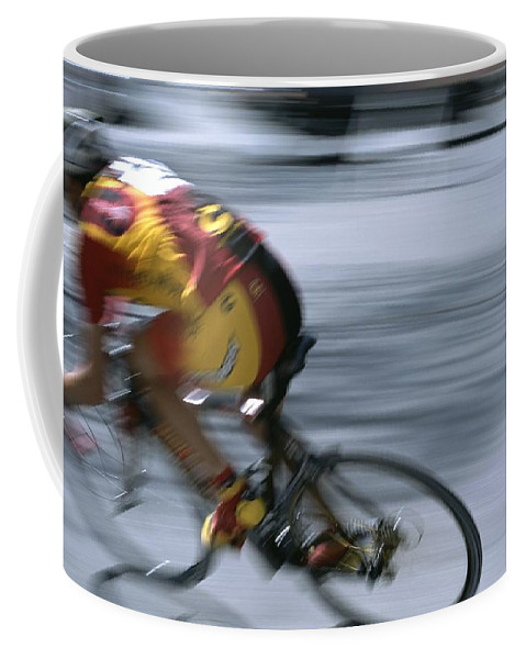 North America Coffee Mug featuring the photograph A Bicyclist Speeds Past In A Race by Heather Perry