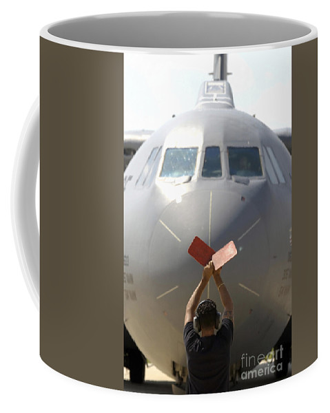 Color Image Coffee Mug featuring the photograph A Crew Chief Marshals In A C-141b by Stocktrek Images