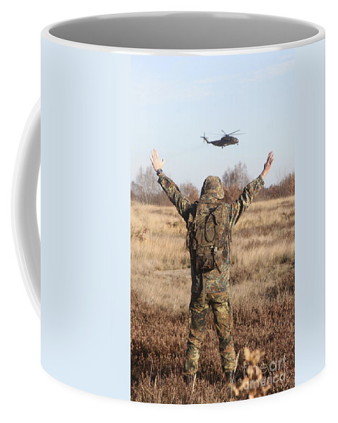 Germany Coffee Mug featuring the photograph A German Army Soldier Guides A Ch-53gs by Timm Ziegenthaler