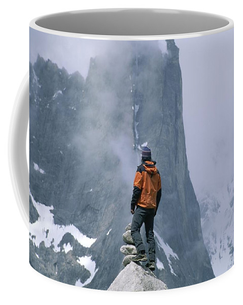 Cliffs Coffee Mug featuring the photograph A Man Stands On A Cliff Watching by Jimmy Chin