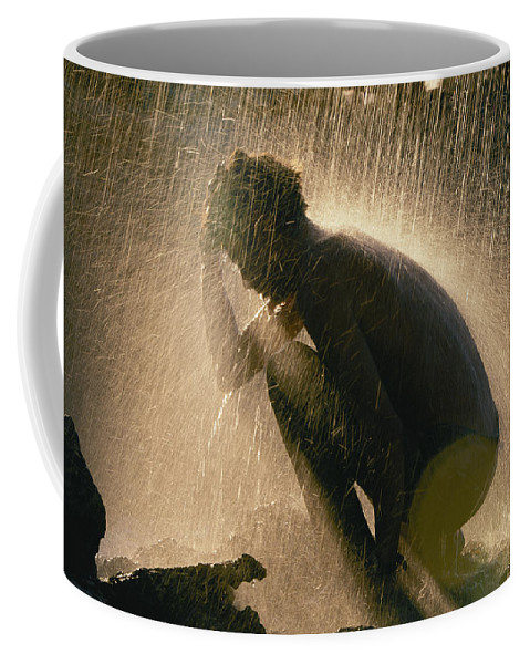 Color Image Coffee Mug featuring the photograph A Silhouetted Man Cooling Off In Water by Carsten Peter