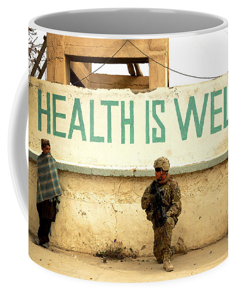 Village Coffee Mug featuring the photograph A Soldier Talks To An Afghan Boy by Stocktrek Images