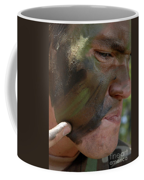 Airman Coffee Mug featuring the photograph Airman Applies War Paint To His Face by Stocktrek Images