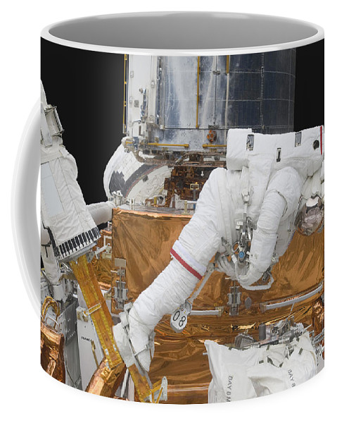 Gravity Coffee Mug featuring the photograph Astronaut Working On The Hubble Space by Stocktrek Images
