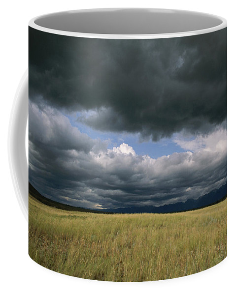 North America Coffee Mug featuring the photograph Dark Clouds Gather Over A Prairie by Annie Griffiths