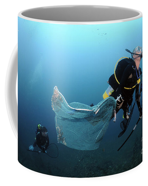 Atlantic Ocean Coffee Mug featuring the photograph Diver Removes Invasive Indo-pacific by Karen Doody
