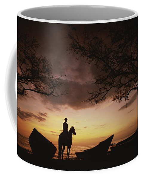 Central America Coffee Mug featuring the photograph Horseback Rider Silhouetted On A Beach by Michael Melford