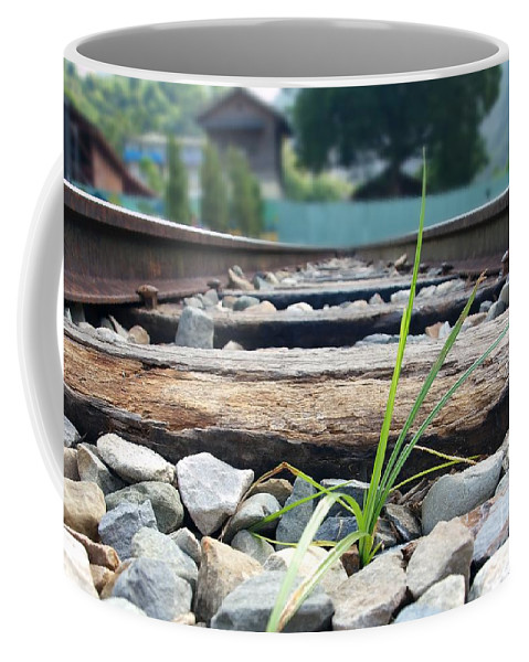 Grass Coffee Mug featuring the photograph Lone Blade Of Grass On Railtracks by Yali Shi