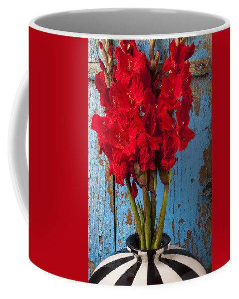 Red Gladiolus Coffee Mug featuring the photograph Red Glads Against Blue Wall by Garry Gay