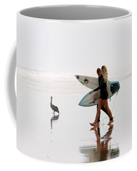 Surfers Coffee Mug featuring the photograph Surfers And A Pelican by Alice Gipson