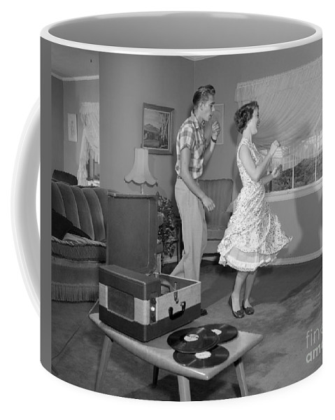 33 Rpm Coffee Mug featuring the photograph Teen Couple Dancing At Home, C.1950s by Debrocke/ClassicStock