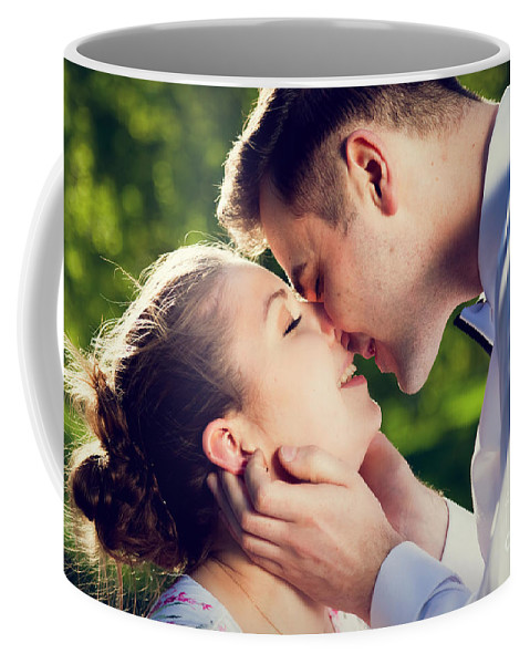 Kiss Coffee Mug featuring the photograph Young Romantic Couple Kissing With Love In Summer Park by Michal Bednarek