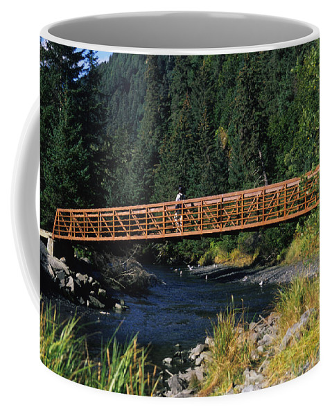 Seward Coffee Mug featuring the photograph A Hiker Crosses A Bridge by Stacy Gold