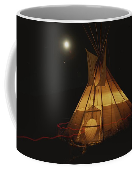North America Coffee Mug featuring the photograph A Tepee Is Illuminated by Michael Melford