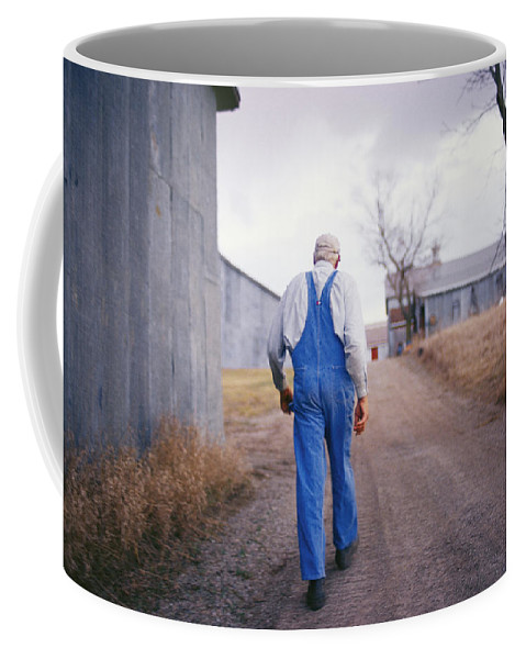 Scenes And Views Coffee Mug featuring the photograph An Elderly Farmer In Overalls Walks by Joel Sartore