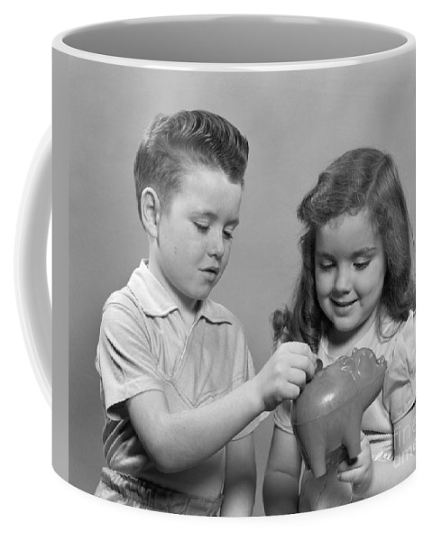 1950s Coffee Mug featuring the photograph Boy And Girl Putting Money Into Piggy by H. Armstrong Roberts/ClassicStock