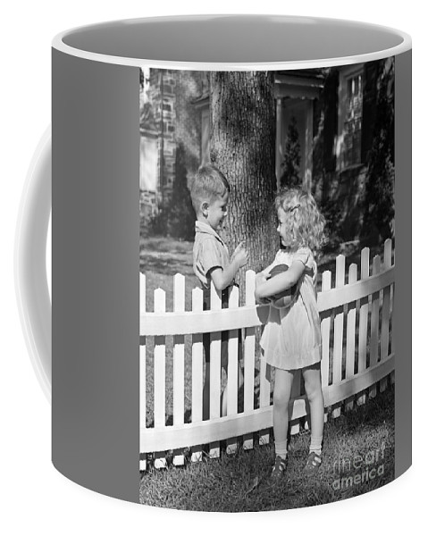 1940s Coffee Mug featuring the photograph Boy And Girl Talking Over Fence, C.1940s by H. Armstrong Roberts/ClassicStock