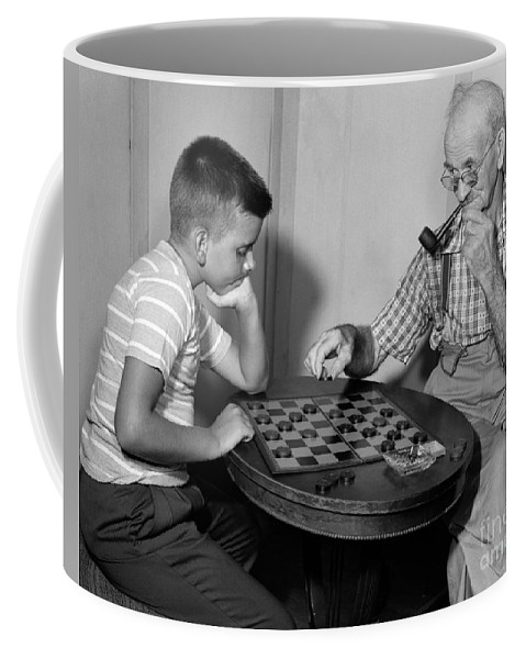 1950s Coffee Mug featuring the photograph Boy Playing Checkers With Grandfather by Debrocke/ClassicStock